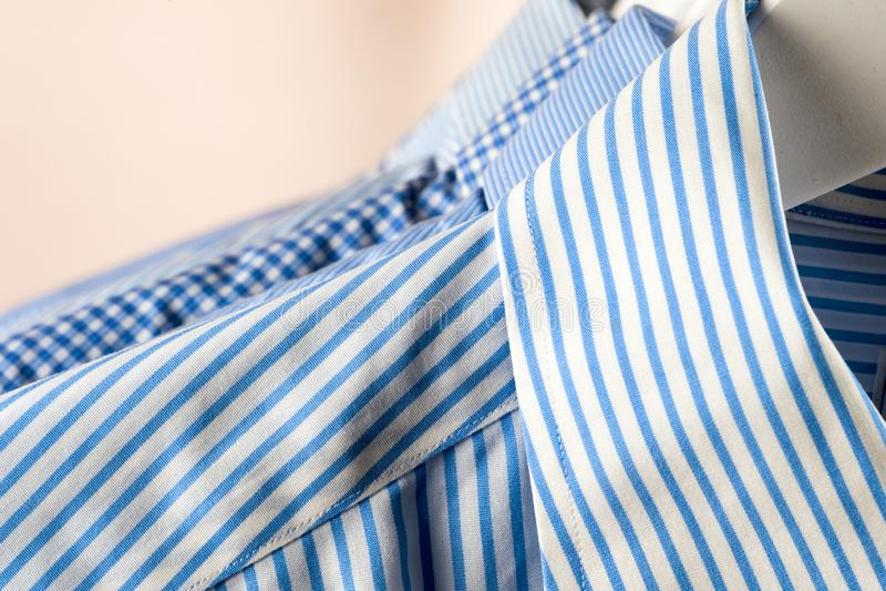 Κρεμάστρες υφασμάτων με τα πουκάμισα Επιχειρησιακά ενδύματα ατόμων o στοκ εικόνα
