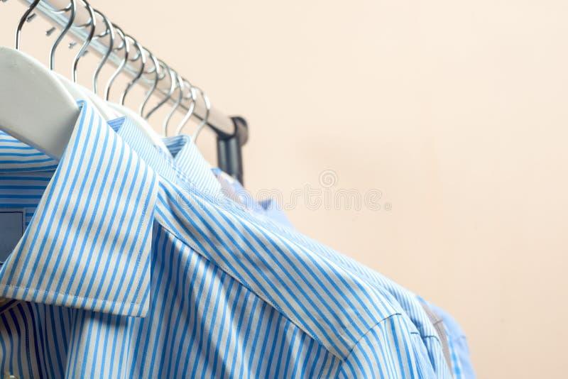 Κρεμάστρες υφασμάτων με τα πουκάμισα Επιχειρησιακά ενδύματα ατόμων ` s Μόδα στοκ φωτογραφία με δικαίωμα ελεύθερης χρήσης