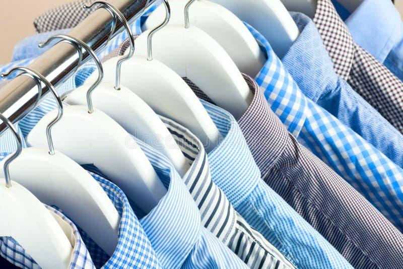 Κρεμάστρες υφασμάτων με τα πουκάμισα Επιχειρησιακά ενδύματα ατόμων ` s Μόδα στοκ εικόνες με δικαίωμα ελεύθερης χρήσης