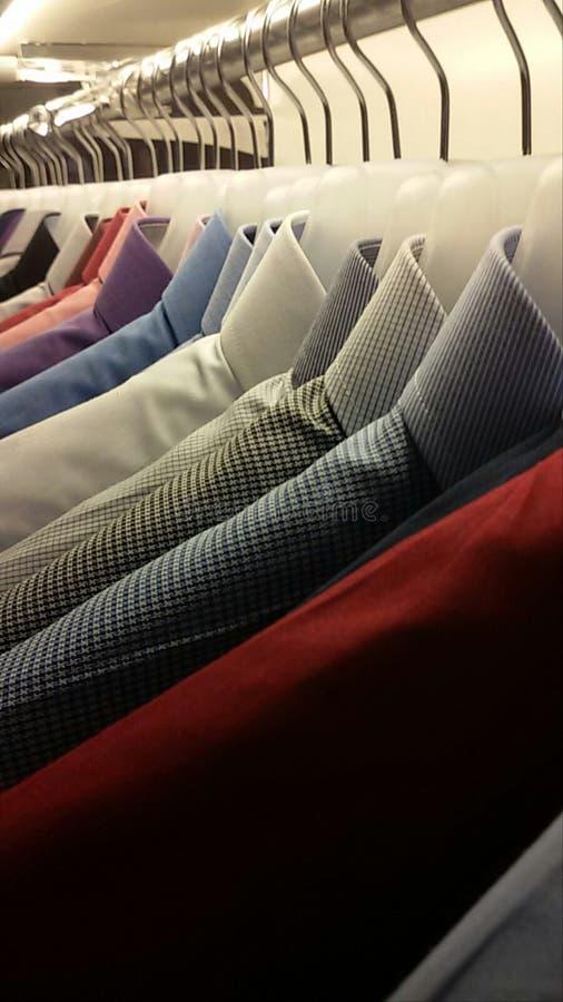 Κρεμάστρες υφασμάτων με τα πουκάμισα στοκ εικόνα