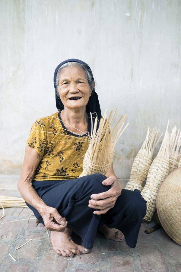 Κρεμασμένα γεν, Βιετνάμ - 26 Ιουλίου 2015: Η ηλικιωμένη γυναίκα υφαίνει την παγίδα ψαριών μπαμπού στο βιετναμέζικο παραδοσιακό χω στοκ φωτογραφία με δικαίωμα ελεύθερης χρήσης