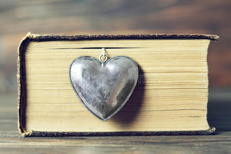 Κρεμαστό κόσμημα καρδιών και εκλεκτής ποιότητας βιβλίο στοκ εικόνα