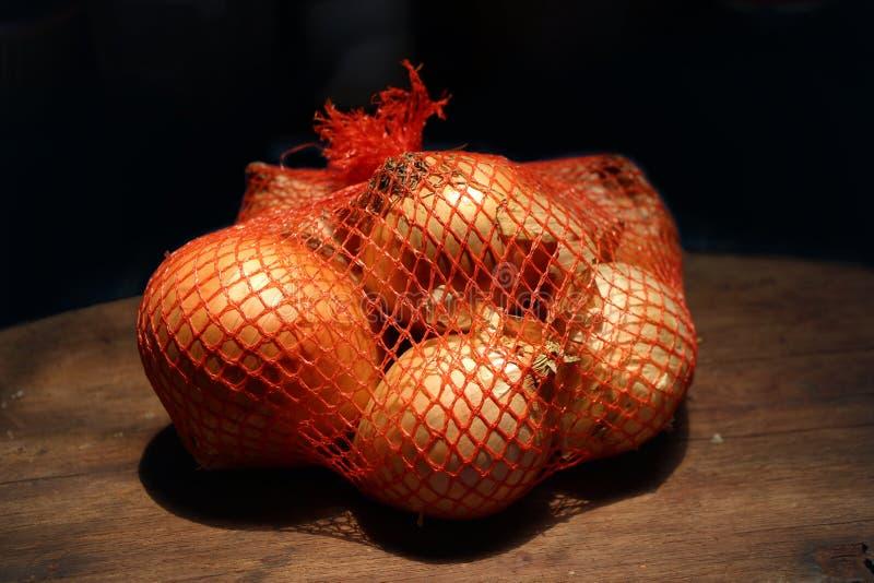 Κρεμμύδια στις τσάντες σε ξύλινο στοκ εικόνα με δικαίωμα ελεύθερης χρήσης