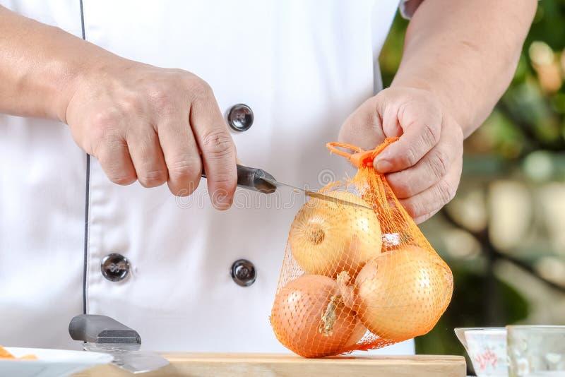 Κρεμμύδια αποφλοίωσης αρχιμαγείρων στοκ φωτογραφία με δικαίωμα ελεύθερης χρήσης