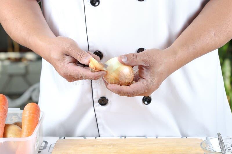 Κρεμμύδια αποφλοίωσης αρχιμαγείρων στοκ εικόνα με δικαίωμα ελεύθερης χρήσης