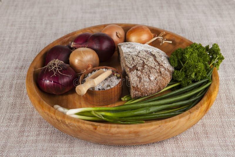 Κρεμμύδια, καφετής ξύλινος δίσκος ψωμιού με το μαϊντανό και άλας και σέλινο στοκ εικόνες