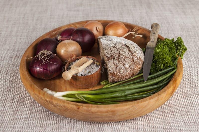 Κρεμμύδια, καφετής ξύλινος δίσκος ψωμιού με το μαϊντανό και άλας και σέλινο, μαχαίρι στοκ φωτογραφία