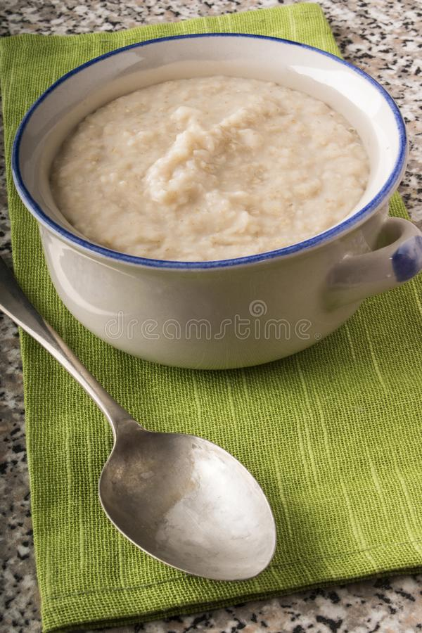 Κρεμώδες κουάκερ που γίνεται με παραδοσιακό ιρλανδικό oatmeal σε ένα κύπελλο στοκ φωτογραφία