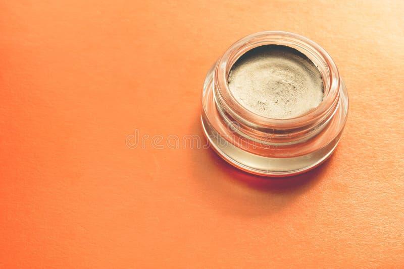 Κρεμώδης σκιά ματιών με μια μεταλλική επίδραση σε ένα βάζο γυαλιού στο πορτοκαλί υπόβαθρο στοκ εικόνες