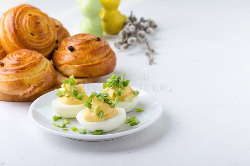 Κρεμώδης τα αυγά και τα γλυκά κουλούρια ρόλων στον εορταστικό πίνακα Πάσχας στοκ εικόνες