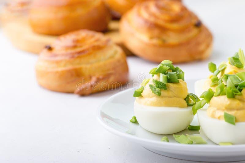 Κρεμώδης τα αυγά και τα γλυκά κουλούρια ρόλων στον εορταστικό πίνακα Πάσχας στοκ φωτογραφία με δικαίωμα ελεύθερης χρήσης