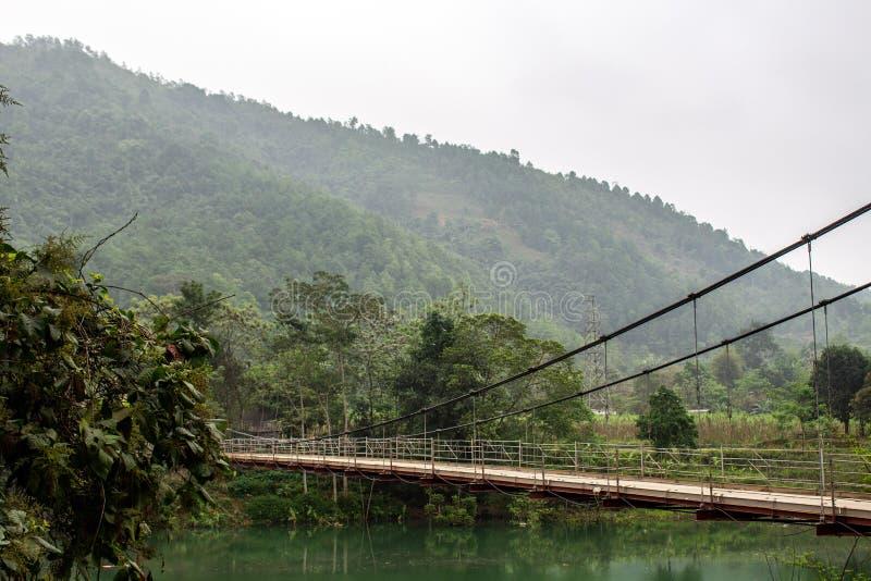 Κρεμώντας γέφυρα που περιβάλλεται από τα πράσινες βουνά και τη ζούγκλα Βιετνάμ στοκ εικόνες