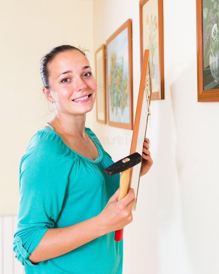 Κρεμώντας εικόνες κοριτσιών στα πλαίσια στον τοίχο στο σπίτι στοκ φωτογραφία με δικαίωμα ελεύθερης χρήσης