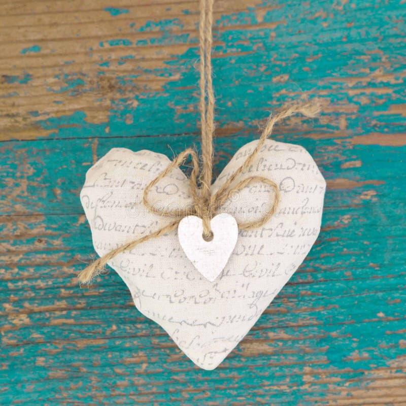 Κρεμώντας καρδιά και τυρκουάζ ξύλινο υπόβαθρο στο ύφος χωρών. στοκ φωτογραφία