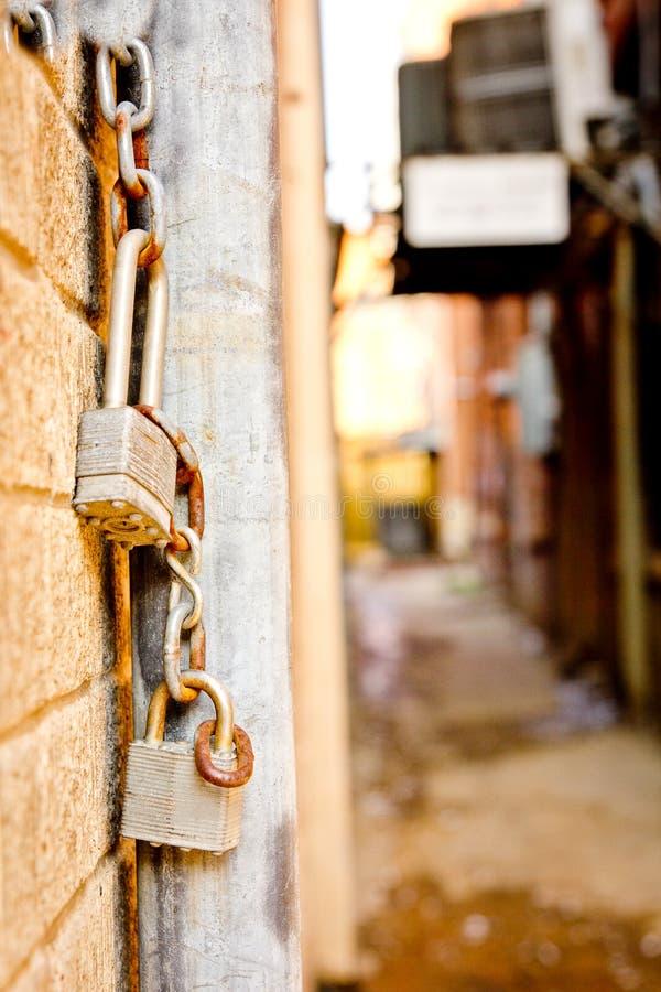 Κρεμώντας κλειδαριές και αλυσίδες κοντά στην αλέα μεταξύ των κτηρίων στοκ φωτογραφία με δικαίωμα ελεύθερης χρήσης