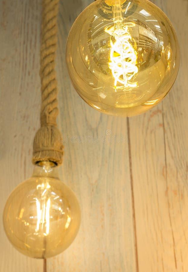 Κρεμώντας λάμπες φωτός πέρα από το ξεπερασμένο ξύλινο υπόβαθρο στοκ εικόνα