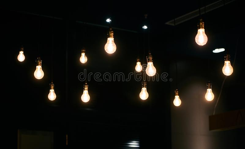 Κρεμώντας υπόβαθρο λαμπών φωτός στο σκοτεινό δωμάτιο στοκ εικόνα