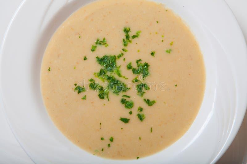 Κρεμώδης σούπα λαχανικών με τα φρέσκα χορτάρια σε ένα άσπρο κύπελλο στοκ εικόνα