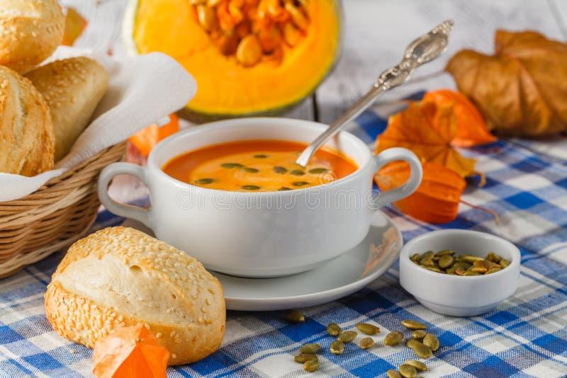 Κρεμώδης σούπα κολοκύθας που ολοκληρώνεται με τους σπόρους και την κρέμα κολοκύθας σε ένα whi στοκ εικόνα