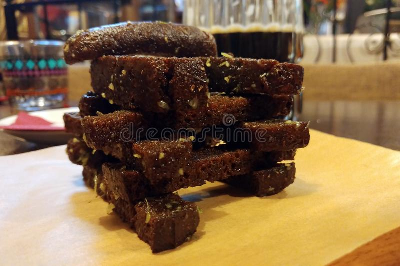 Κροτίδες με το σκόρδο από το μαύρο ψωμί στο πετρέλαιο σε μια ξύλινη στάση Μεγάλα καφετιά croutons στοκ φωτογραφίες