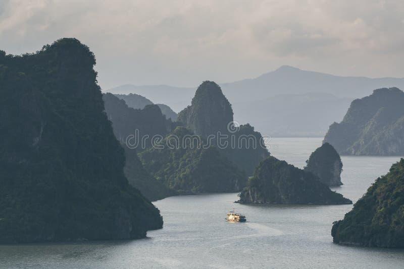 Κρουαζιερόπλοιο τουριστών που πλέει μεταξύ των βουνών ασβεστόλιθων στον κόλπο Halong, Βιετνάμ στοκ εικόνα