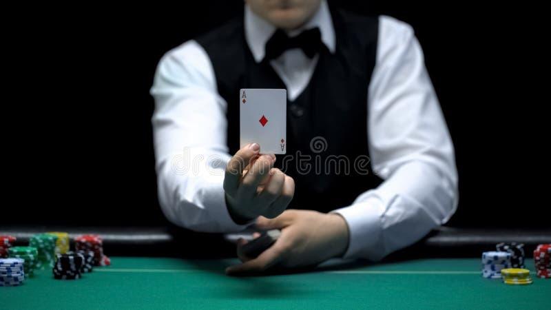 Κρουπιέρης χαρτοπαικτικών λεσχών που παρουσιάζει κάρτα άσσων μπροστά από τη κάμερα, τεχνάσματα μετάθεσης παιχνιδιών πόκερ στοκ εικόνες