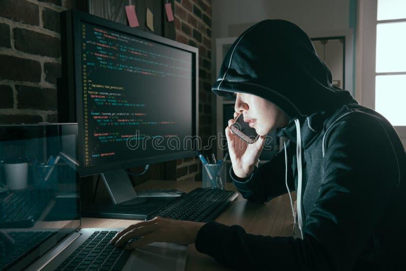 Κρυμμένο γυναίκα πρόσωπο χάκερ που χρησιμοποιεί το κινητό τηλέφωνο κυττάρων στοκ φωτογραφία με δικαίωμα ελεύθερης χρήσης