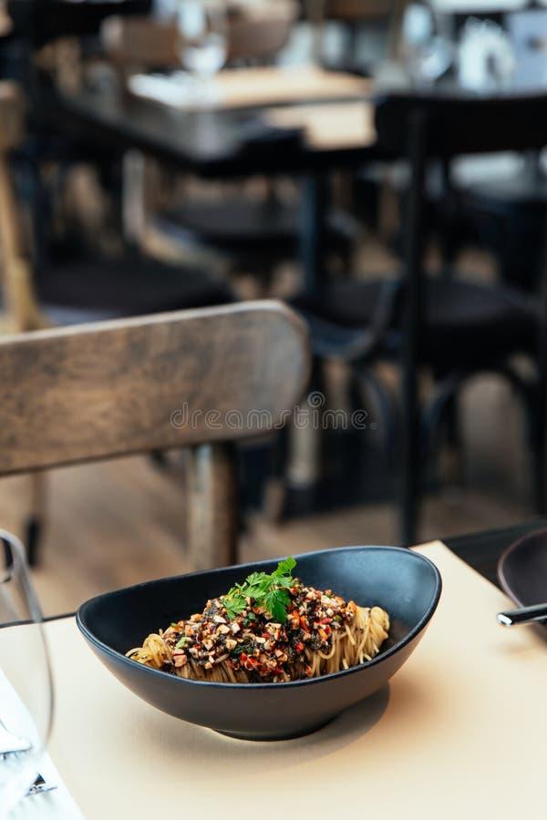 Κρύα ζυμαρικά Capellini με το φύκι Hikiji, τον κατεψυγμένους αστακό και την ουσία τρουφών, που εξυπηρετούνται στο μαύρο κύπελλο στοκ εικόνες
