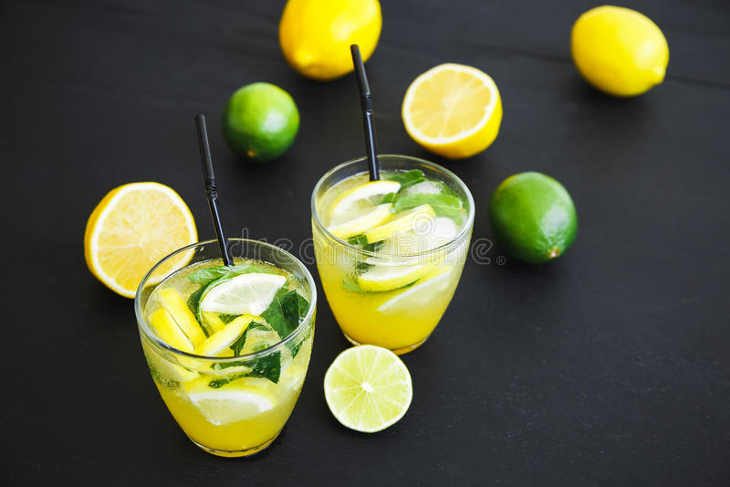 Κρύα και αναζωογονώντας λεμονάδα με το λεμόνι και τους ασβέστες Φρέσκια νόστιμη λεμονάδα στοκ εικόνες