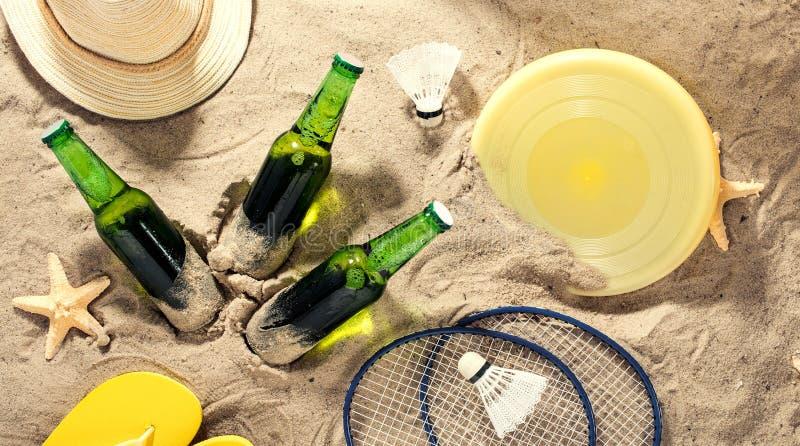 Κρύα μπύρα ξανθού γερμανικού ζύού με τα στοιχεία για τις δραστηριότητες παραλιών στην άμμο απεικόνιση αποθεμάτων