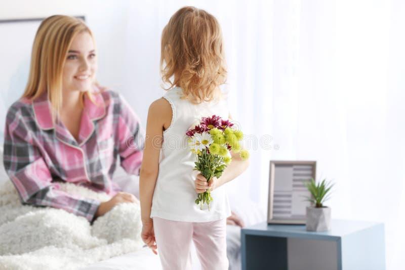 Κρύβοντας ανθοδέσμη μικρών κοριτσιών των λουλουδιών για τη μητέρα της πίσω από την πλάτη στοκ φωτογραφίες με δικαίωμα ελεύθερης χρήσης