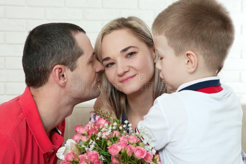 Κρύβοντας ανθοδέσμη γιων στην αιφνιδιαστική μαμά την ημέρα μητέρων ` s γυναίκα, άνδρας στοκ εικόνα
