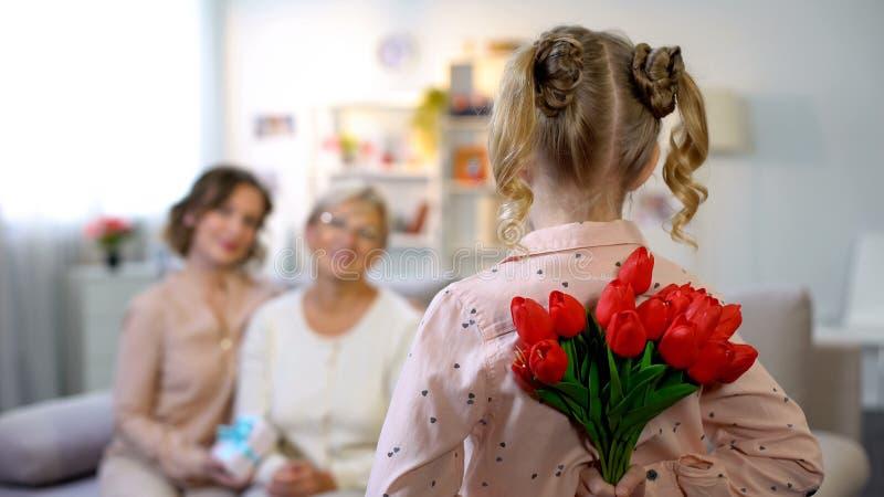 Κρύβοντας τουλίπες μικρών κοριτσιών για τη γιαγιά, εορτασμός ημέρας μητέρων, έκπληξη στοκ εικόνες με δικαίωμα ελεύθερης χρήσης