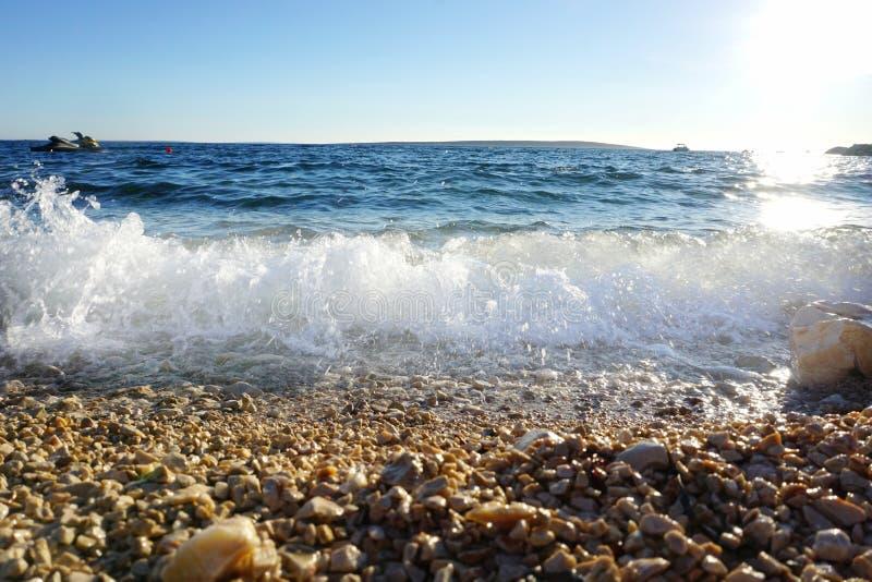Κρύσταλλο - σαφές μπλε θαλάσσιο νερό με τα κύματα και την ήττα αφρού θάλασσας στην παραλία ακτών και χαλικιών στοκ εικόνες με δικαίωμα ελεύθερης χρήσης