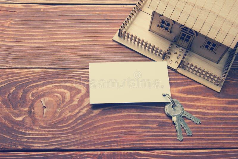 κτήμα έννοιας πραγματικό Πρότυπο σπίτι, κλειδιά, κενή επαγγελματική κάρτα στον ξύλινο πίνακα Τοπ όψη εικόνα που τονίζεται στοκ εικόνες