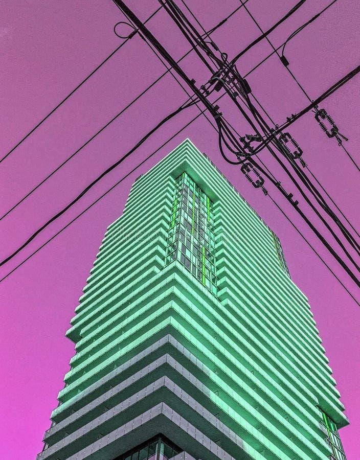 Κτήριο πολυόροφων κτιρίων με την πράσινη πυράκτωση ενάντια στον πορφυρό ουρανό και τα μαύρα καλώδια δύναμης στοκ εικόνες με δικαίωμα ελεύθερης χρήσης