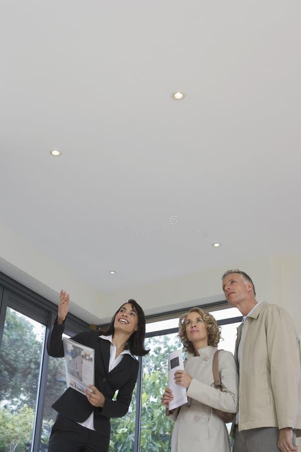 Κτηματομεσίτης και ζεύγος που παρατηρούν τη νέα ιδιοκτησία στοκ φωτογραφίες