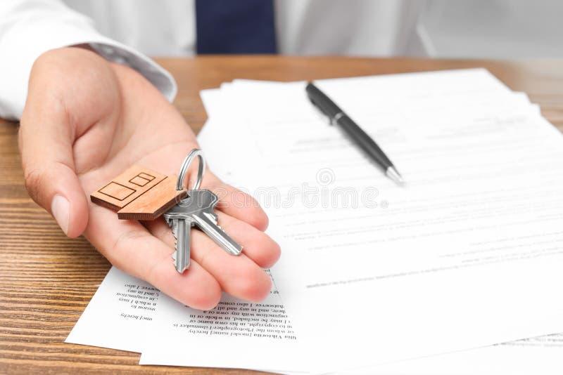 Κτηματομεσίτης με τα κλειδιά και τα έγγραφα στοκ εικόνα