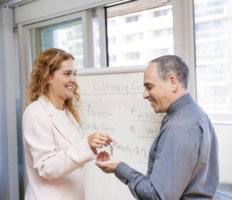 Κτηματομεσίτης που δίνει τα κλειδιά στον πελάτη στοκ εικόνες