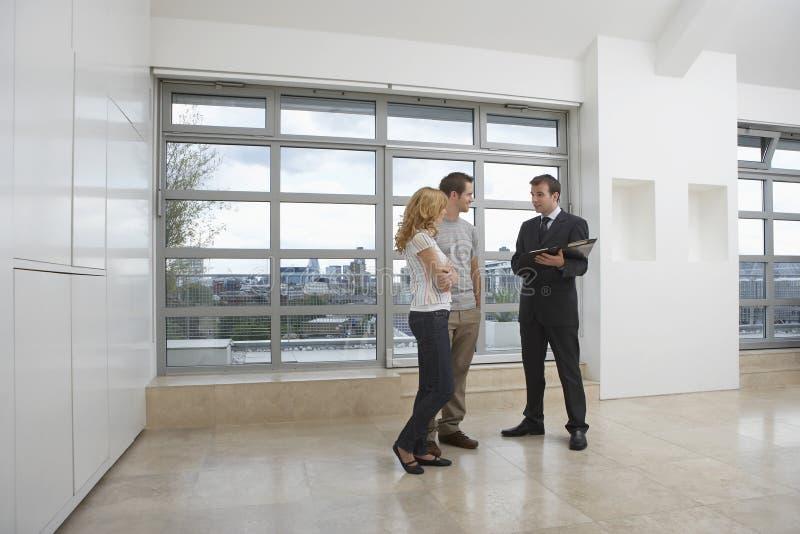 Κτηματομεσίτης που παρουσιάζει στο ζεύγος νέο διαμέρισμα στοκ φωτογραφία με δικαίωμα ελεύθερης χρήσης