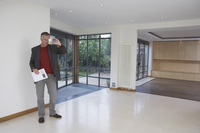 Κτηματομεσίτης που φωτογραφίζει τη νέα ιδιοκτησία στοκ φωτογραφίες