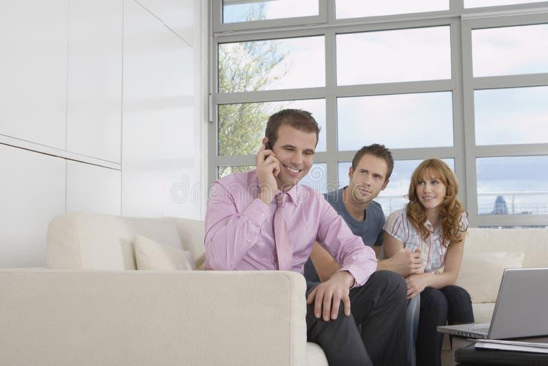 Κτηματομεσίτης στην κλήση από το ζεύγος στο νέο σπίτι στοκ εικόνες