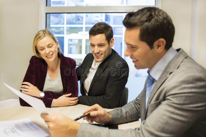 Κτηματομεσίτης συνεδρίασης του ζεύγους για να αγοράσει την ιδιοκτησία στοκ φωτογραφία με δικαίωμα ελεύθερης χρήσης