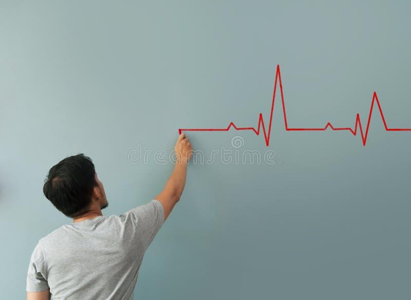 Κτύπος της καρδιάς σχεδίων ατόμων με την κόκκινη κιμωλία στον τοίχο στοκ εικόνα με δικαίωμα ελεύθερης χρήσης