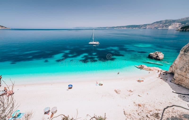 Κυανό νερό της παραλίας Fteri, Cephalonia Kefalonia, Ελλάδα Άσπρο γιοτ καταμαράν στο σαφές μπλε θαλάσσιο νερό Τουρίστες επάνω στοκ φωτογραφίες με δικαίωμα ελεύθερης χρήσης