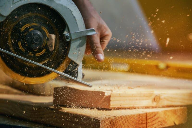 κυκλικό στενό πριόνι λεπίδων που αυξάνεται Ξυλουργός που χρησιμοποιεί το κυκλικό πριόνι για την ξύλινη ακτίνα στοκ φωτογραφία με δικαίωμα ελεύθερης χρήσης