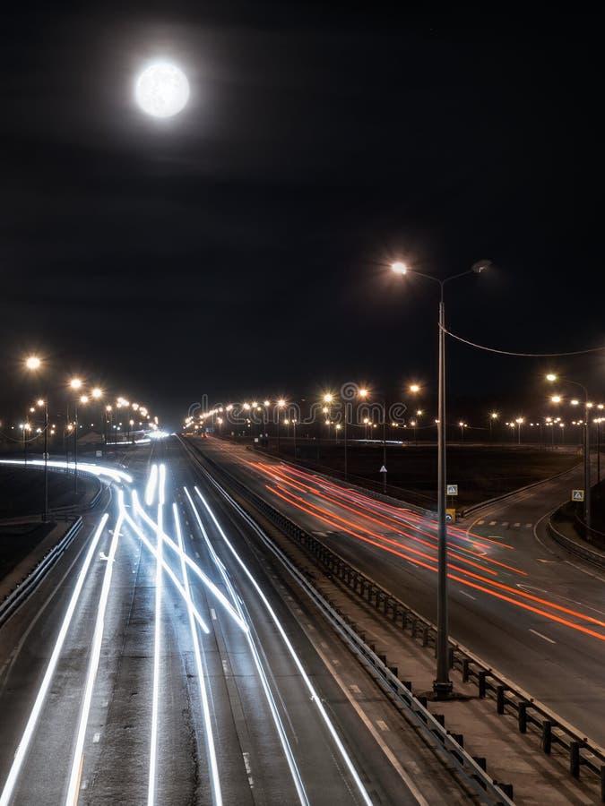 Κυκλοφορία πόλεων νύχτας με τη φωτεινή πανσέληνο στον ομιχλώδη ουρανό στοκ εικόνες