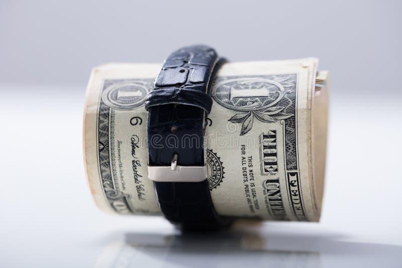 Κυλημένα επάνω τραπεζογραμμάτια δολαρίων που δένονται με τη ζώνη στοκ φωτογραφίες