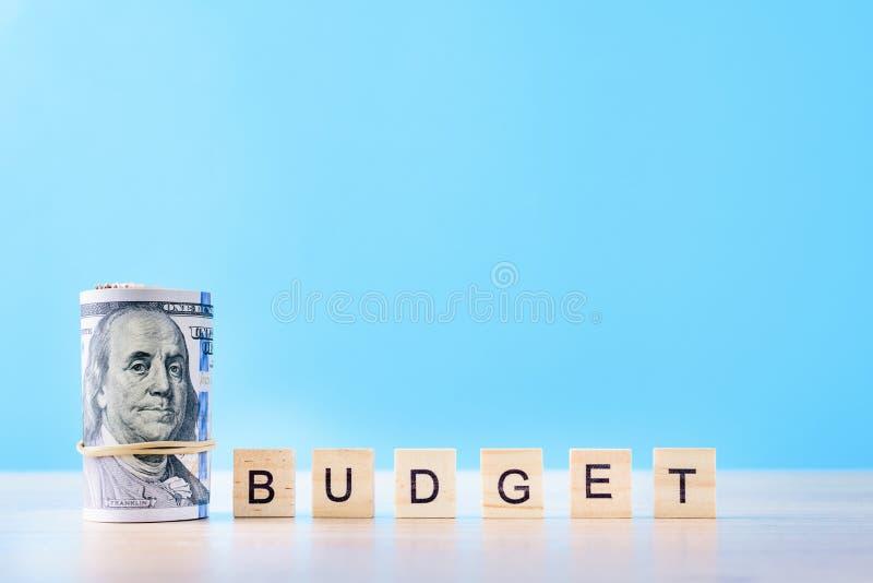 Κυλημένοι επάνω λογαριασμοί δολαρίων και προϋπολογισμός λέξης σε ένα μπλε υπόβαθρο Έννοια λογιστικής χρηματοδότησης στοκ εικόνες