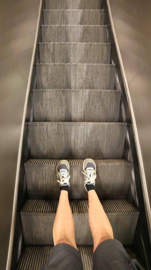 Κυλιόμενη σκάλα ενός εμπορικού κέντρου και τα πόδια του τουρίστα με στοκ φωτογραφία